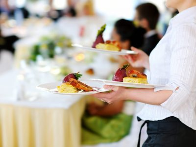 Waitress carrying three plates with meat dish on some festive event, party or wedding reception